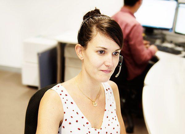 Staff member wearing headset working at desk