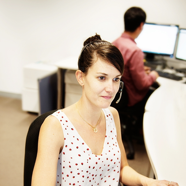 Staff member wearing headset working at desk