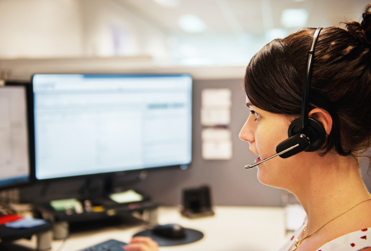 women with headset on working at computer