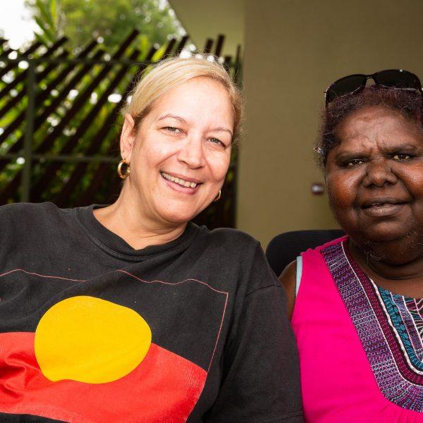Woman wearing Aboriginal flag shirt next to woman wearing pink shirt