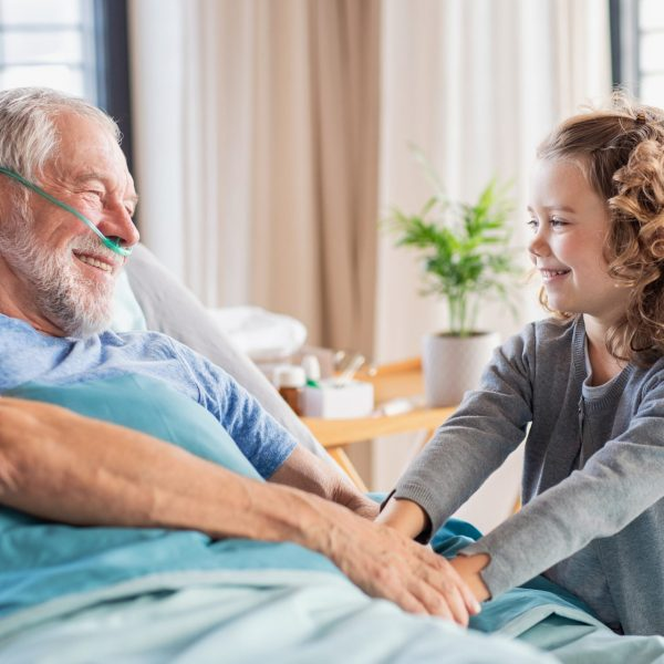 Man in hospital bed holding hands with young girl
